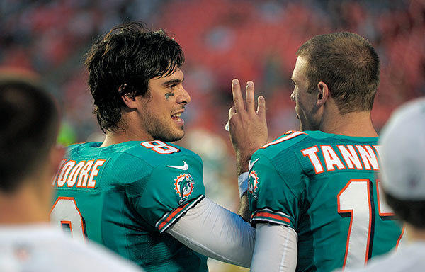 Miami Dolphins quarterbacks Matt Moore and Ryan Tannehill talks on the sidelines during the first quarter of their preseason game against the Tampa Bay Buccaneers, Friday, August 10, 2012, at Sun Life Stadium.