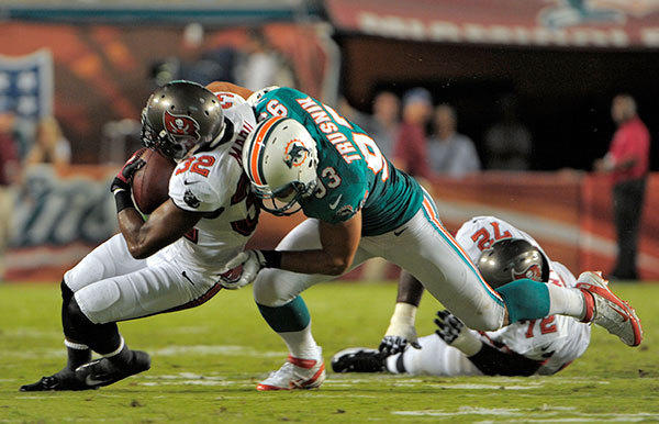 Miami Dolphins linebacker Jason Trusnik tackles Tampa Bay Buccaneers running back Mossis Madu, during the second quarter of their preseason game, Friday, August 10, 2012, at Sun Life Stadium.