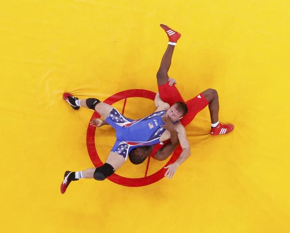 Jake Herbert of U.S. (in blue) fights with Cuba's Humberto Arencibia Martinez in Men's 84Kg Freestyle wrestling action Saturday.