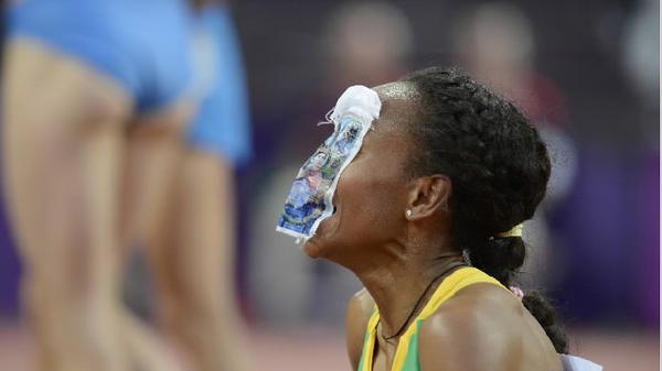 Ethiopia's Meseret Defar puts a drawing of the Virgin Mary on her face as she celebrates winning gold in the women's 5000m final at the athletics event of the London 2012 Olympic Games.