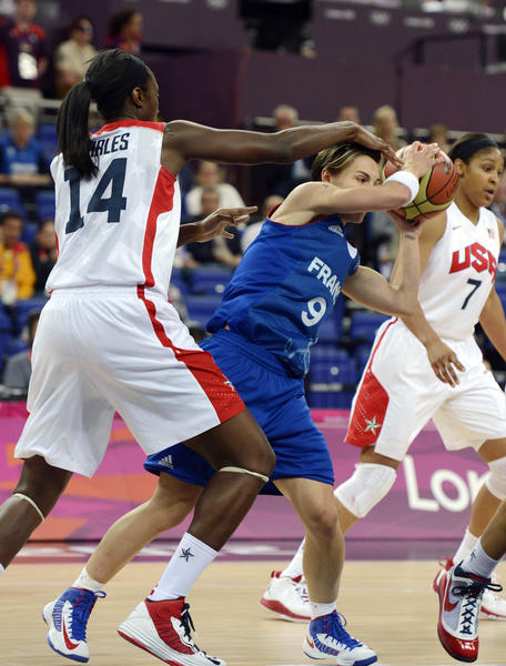 France guard Celine Dumerc (9) holds the ball away from USA center Tina Charles (14) during the women's basketball gold medal game in the London 2012 Olympic Games at North Greenwich Arena.