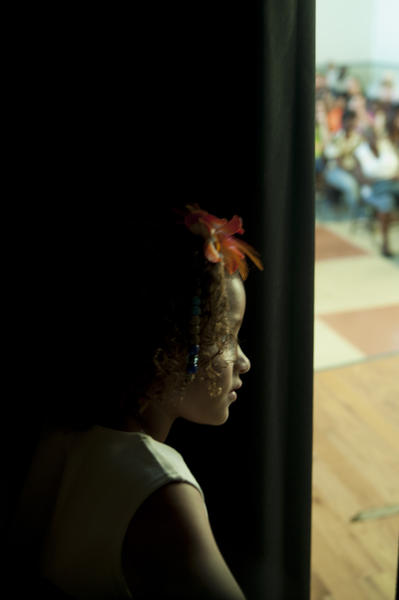 Jada Pallanck, 8, of West Baltimore, peeks through a gap in the curtains backstage to see the performers and audience.