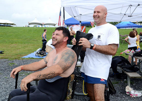 Veteran Bill Hannigan of Ronkonkoma, NY, in wheelchair, enjoys a laugh as he is assisted with putting on his scuba diving suit by Ray Ruffin of Point Pleasant, Pa., right. After his military service Hannigan was paralyzed after a motorcycle accident.