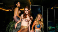 Situated on a faux rock, three beautiful mermaids wearing colorful tails and seashell bras greeted each guest who walked into the Wyndham Orlando convention hall Saturday.