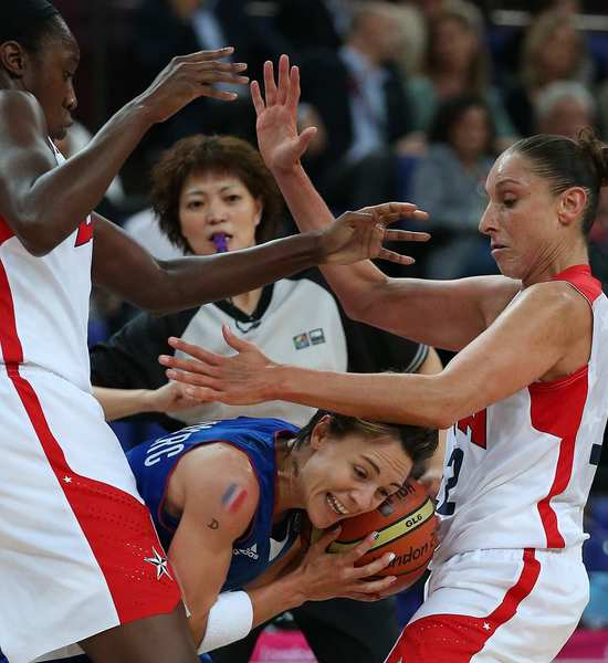 France's Celine Dumerc is trapped by U.S. defenders Tina Charles, left, and Diana Taurasi.