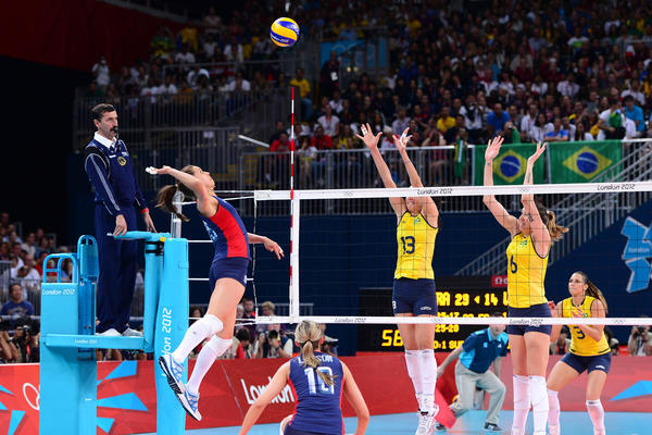 Weak-side hitter Logan Tom spikes the ball against Brazil's Sheilla Castro and Thaisa Menezes.