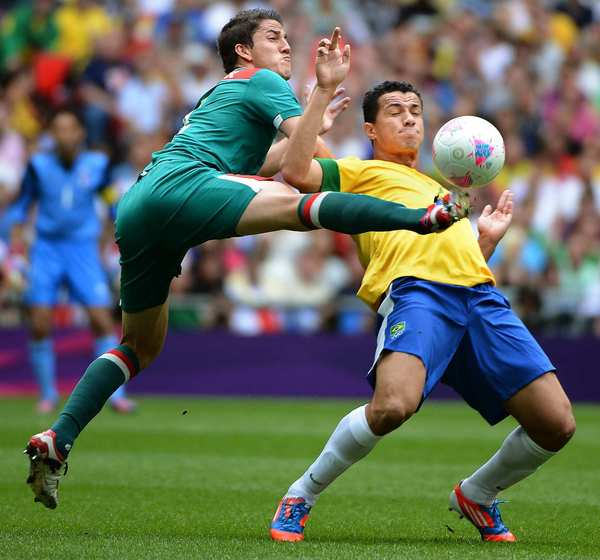Mexico's Hiram Mier, left, battles Brazil's Leandro Damiao for the ball in the men's gold medal soccer match won by Mexico, 2-1.