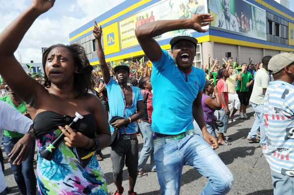 Jamaicans celebrate in the Half Way Tree neighborhood of Kingston, Jamaica after Usain Bolt and teammates won the men's 4x100-meter relay gold medal and broke the world record.