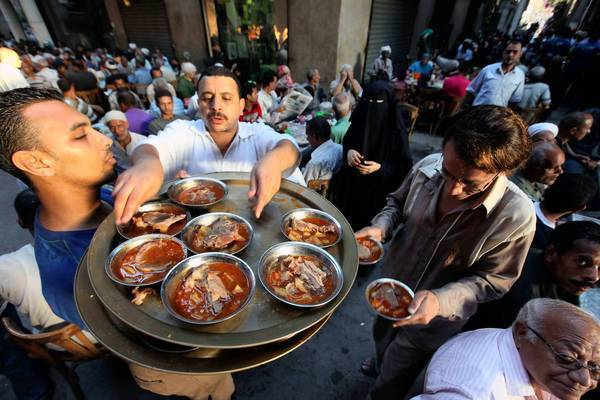 "Muslims are handed a free meal in a Ramadan ""Merciful Banquet"" tent as they wait to break their fast in Cairo."