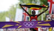 Uganda's Stephen Kiprotich celebrates as he crosses the finish line to win the athletics event men's marathon during the London 2012 Olympic Games