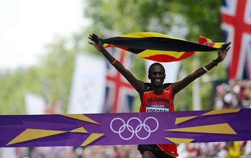 Uganda's Stephen Kiprotich celebrates as he crosses the finish line to win the athletics event men's marathon during the London 2012 Olympic Games.