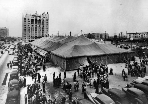 "Graham's 1949 ""Canvas Cathedral"" tent revival, at Hill Street and Washington Boulevard in Los Angeles. The event, and Graham, got a major boost from publishing magnate William Randolph Hearst."