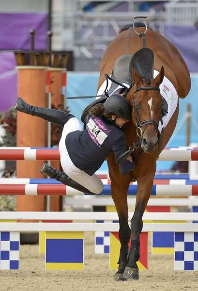 Tamara Vega of Mexico falls off her horse after she jumps an obstacle during the modern pentathlon horse jumping round at Greenwich Park for the London 2012 Olympic Games.