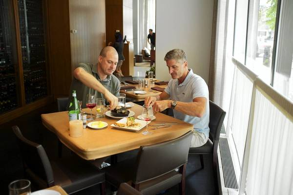 "John Flippen and Jeff Lex work on an appetizer at David Burke's Primehouse, where a recently revamped menu is designed for a business lunch. The restaurant offers a ""Caesarista,"" who makes your Caesar salad tableside."