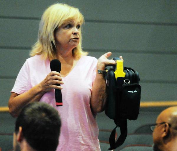 Rachel Moyer of Shawnee on the Delaware holds an automated external defibrillator during a presentation about sudden cardiac arrest on Thursday at Emmaus High School. Moyer always carries an AED with her since her son died from sudden cardiac arrest in 2000. A new state law requires annual training on signs and symptoms of the condition.