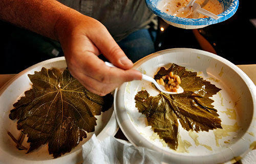 Making dolmas (stuffed grape leaves). Click here for the recipe.