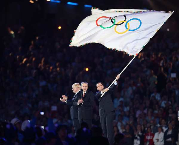 Rio de Janeiro mayor Eduardo Paes waves the Olympic flag after receiving it from London mayor Boris Johnson, left, via Jacques Rogge, president of the International Olympic Committee, during the traditional handover ceremony in London.