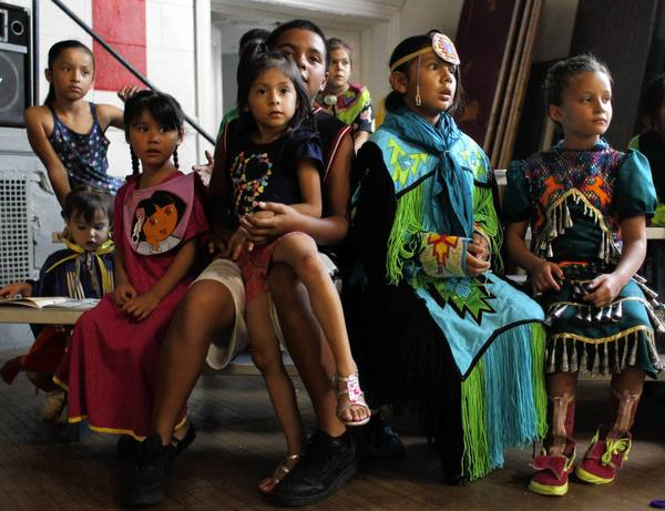 Young American Indian dancers, some in traditional clothing, wait to be called at a back-to-school event this month sponsored by the American Indian Center at its Uptown site.