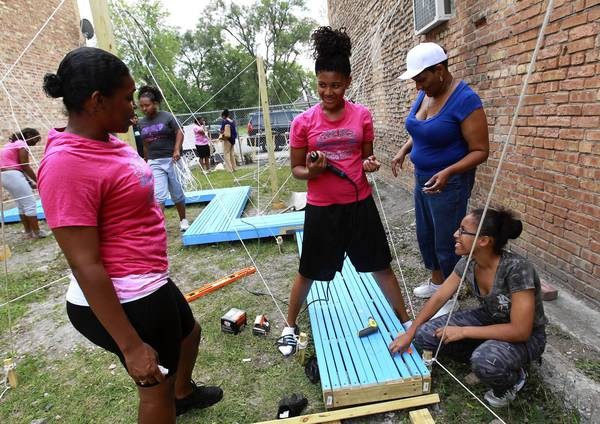 Adrienne Gordon, from left, Jariah Nolan, Darlene Nolan and Stephanie Morris help build a playground on 103rd Street near Wentworth Avenue in Chicago's Roseland community. The young women are among 10, ages 15 to 18, using science, technology, engineering and math (STEM) in the project as part of a program run by the nonprofit Demoiselle 2 Femme.