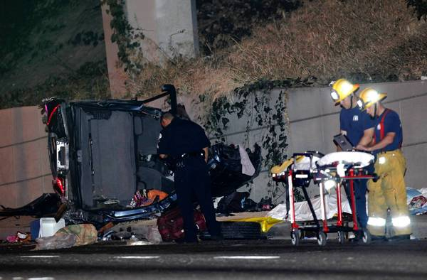 Emergency personnel examine the wreckage of an SUV that fell from a freeway to Figueroa Street on Sunday evening. A man, woman and child were killed. Three others were taken to hospitals.