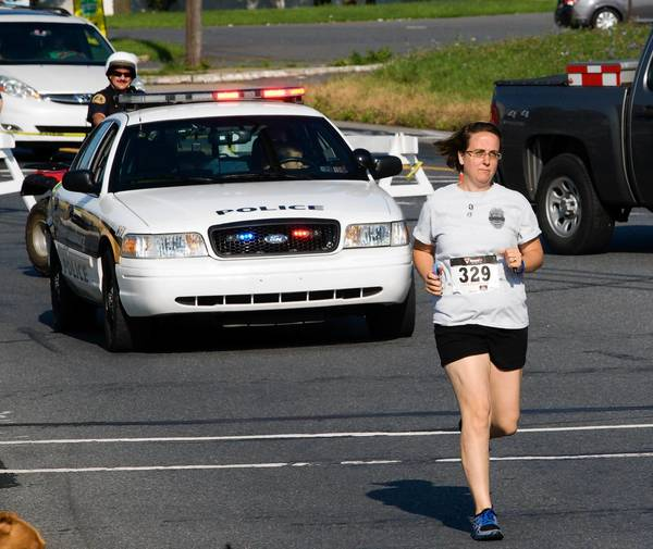 Jennifer Lasso, widow of Freemansburg police officer Robert Lasso, runs along the course of the Memorial 5K recognizing the anniversary of her husband's death in the line of duty Aug. 11, 2011. Proceeds from Sunday's event will be donated to the Lasso family and the Freemansburg police department.