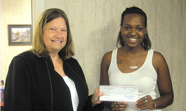 From left, Joanne Ballengee, Hagerstown Housing Authority's deputy director, presents Takaila Warfield with a $2,000 scholarship check.