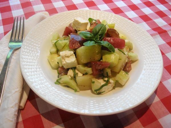 A quick and easy summertime meal: fresh tomatoes and cucumbers tossed with feta cheese and olive oil.