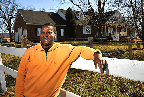 Dickson Tabi, owner of Soma Manor Assisted Living, is pictured outside the facility shortly before it opened in early 2011. Tabi has been charged with reckless endangerment and other counts after an 84-year-old resident fell through a floor, suffering life-threatening injuries.