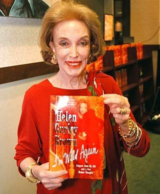 "Helen Gurley Brown holds her book ""I'm Wild Again"" in New York City in 2000."