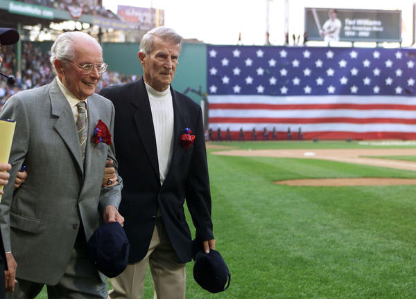 Ted Williams' close friends and teammates Dom Dimaggio (L) and Johnny Pesky (R) take to the field arm in arm at Boston's Fenway Park to honor Ted Williams July 22, 2002 during tribute ceremonies for the Red Sox baseball legend.