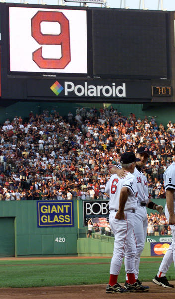 Boston Red Sox All-Star shortstop Nomar Garciaparra (R) puts his arm around former Red Sox star Johnny Pesky at the conclusion of tribute ceremonies for Ted Williams July 5, 2002, at Fenway Park in Boston.