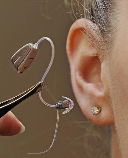 A model displays the world's smallest hearing aid