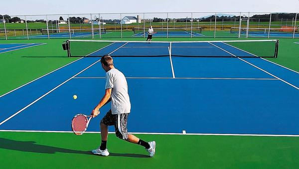 James Buchanan High School tennis players Grant Strawoet, foreground, and Andrew Rupert practice Monday evening on the new tennis courts at the Christine Beddard Tennis Complex in Mercersburg, Pa.