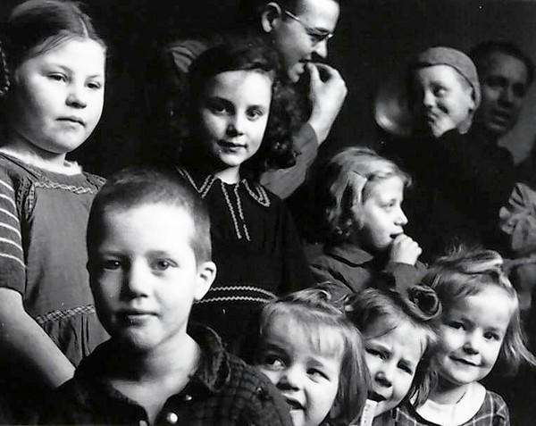 Phil Drell, top center, a combat photographer from the Chicago area, teaches children at a newly freed Belgian orphanage how to chew bubble gum during World War II.