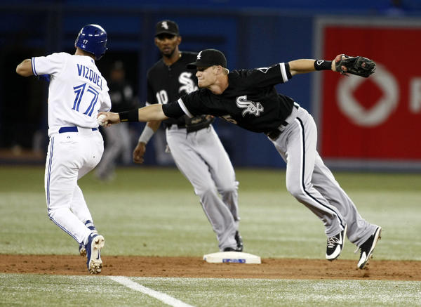 White Sox second baseman Gordon Beckham tags out Blue Jays infielder Omar Vizquel to start a double play during Monday's game.