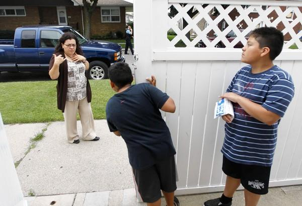 Silvia Villa watches Chicago police officers swarm outside her home in the Westlawn neighborhood as she keeps her sons, Andres 9, left, and Omar, 11, inside their family's gate. Police had caught a suspect earlier and were looking for a discarded weapon.