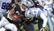 Darren McFadden #20 of the Oakland Raiders gets tackled after a short gain by Gerald Sensabaugh #43 of the Dallas Cowboys