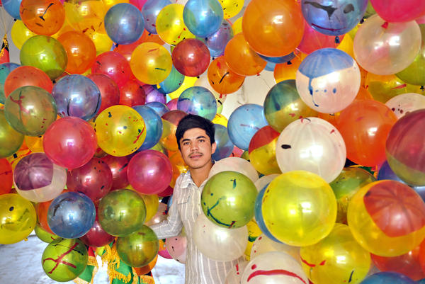 An Afghan young man carries balloons during a welcoming ceremony for the country's athletes at Kabul stadium on August 14, 2012 following the completion of the 2012 London Olympic Games.