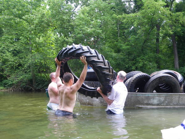 Volunteers hoist old tractor tire into john boat during Gunpowder River cleanup organized by Greater Baltimore Canoe Club