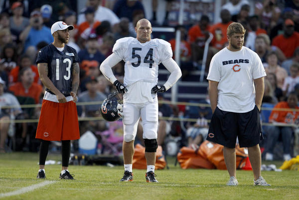 Chicago Bears wide receiver Johnny Knox, left, and linebacker Brian Urlacher, center, wait on the sidelines during training camp at Olivet Nazarene University in Bourbonnais in July.