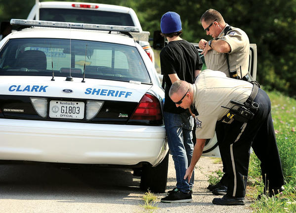 Clark County Deputy Sheriff Chris Douglas, foreground, and Deputy Butch Best check a juvenile before placing him in their cruiser on Boonesboro Road Monday morning. The juvenile was seen allegedly stealing gasoline from a home on Old Boonesboro Road by off-duty special deputy Mark Brown. Brown chased the suspect and called for help.