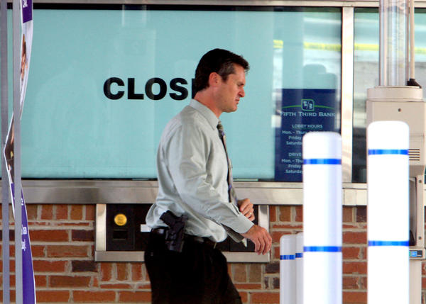 A West Chicago police detective sergeant passes the closed sign on the drive-thru window of the Fifth Third Bank while investigators from the West Chicago Police Department, the DuPage County Sheriff's office and the FBI investigate a morning robbery at the bank in the 1800 block of North Neltor Road. The robber is at large.