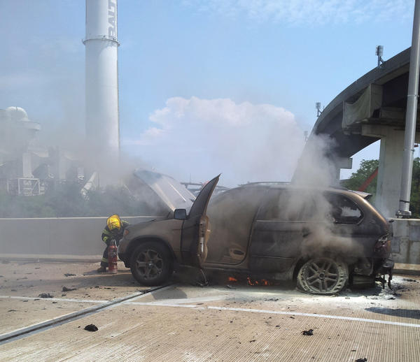 Firefighters extinguish a car that was on fire on I-295 entering the city Aug. 14.