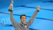 US swimmer Michael Phelps holds his trophy
