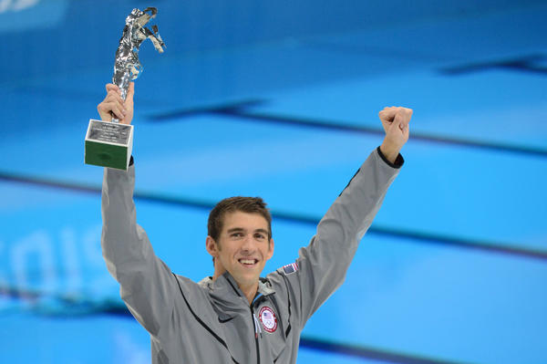 US swimmer Michael Phelps holds his trophy of the greatest olympic athlete of all time after he won gold in the men's 4x100m medley relay final during the swimming event at the London 2012 Olympic Games on August 4, 2012 in London.       AFP PHOTO / CHRISTOPHE SIMONCHRISTOPHE SIMON/AFP/GettyImages ORG XMIT: 148073368