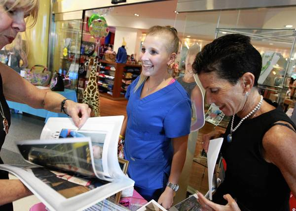 Cancer survivor Yali Derman, center, promotes her designer bags at the Lurie Children's Hospital in August.