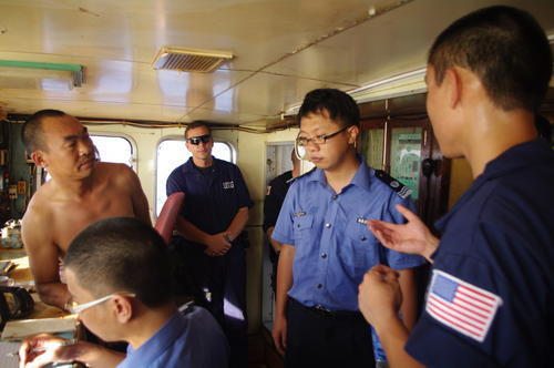Members of the Coast Guard and China Fishery Law Enforcement Command review the records on board the suspected high seas drift net fishing vessel Da Cheng in the North Pacific Ocean Aug. 11, 2012. The crew of the Coast Guard Cutter Rush sighted the Da Cheng and boarded it in accordance with the Western and Central Pacific Fisheries Commission's high seas boarding inspection procedures on July 27.