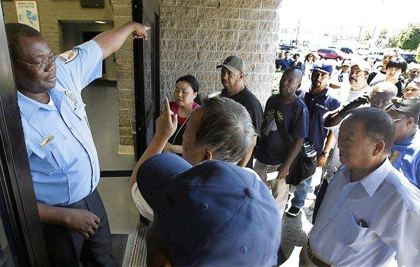 A security guard directs people to the end of a long line outside the DMV office in South Los Angeles on Tuesday. A computer crash at DMV offices statewide left clerks without access to information needed for issuing licenses and vehicle registrations.