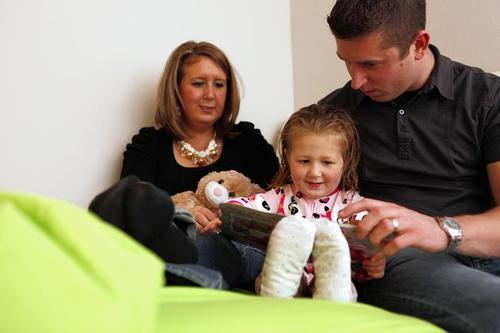 Laura and Kyle Maxwell read to their 2-year-old daughter Emma in their Fayetteville, Ark. apartment. The family sold all their possessions and moved to Fayetteville from Alaska after their seven-week-old son Preston suffocated against a crib bumper in April.