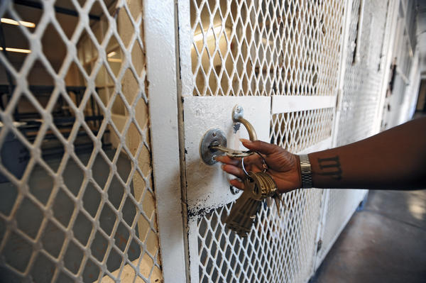 A correctional officer unlocks the gate to a communal cell block during a tour of the annex building at city jail.
